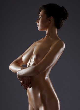 wet breast: Attractive woman posing nude. Her body glistens with sweat