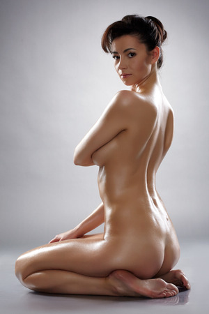 wet breast: Studio shot of beautiful nude woman with wet body, on grey background Stock Photo