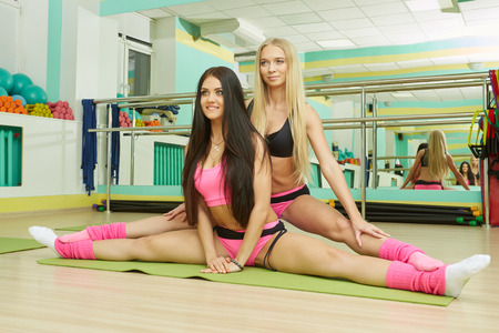 Training session in gym. Sexy women doing stretching exercises