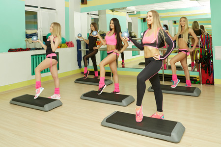 fitness woman: Fitness center. Image of athletic girls training on steppers Stock Photo