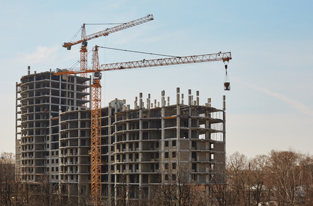 multifamily: Real estate. Image of building under construction and cranes