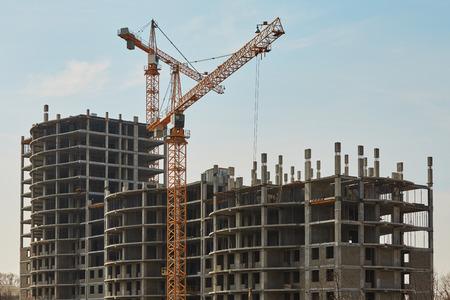 concrete commercial block: Building construction site with cranes under clear sky Stock Photo