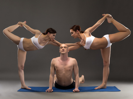 threesome: Yoga composition of flexible people posing at camera Stock Photo