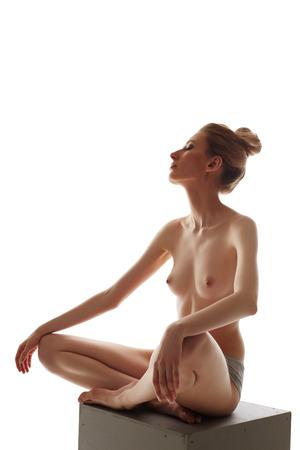 seins nus: Sensuelle femme mince posant topless alors qu'il était assis sur le cube