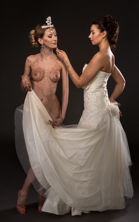 Mehandi art. Image of sensual brides posing in pair, on grey background