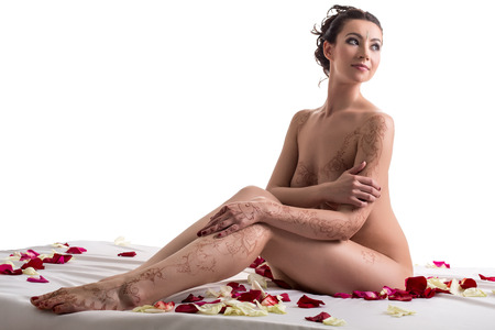 mujeres eroticas: Mehandi. Sonriendo morena posando desnuda en la cama con p�talos de rosa