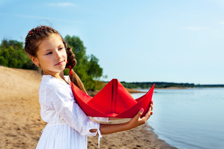 cuddles: Image of sweet little girl cuddles paper boat