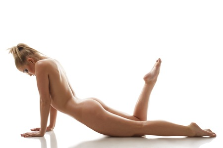nudity young: Seductive naked girl lying in studio, isolated on white