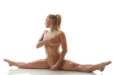 mujeres jovenes desnudas: El estiramiento. Desnudo chica sudorosa hace fractura gimnasia, aislado en blanco Foto de archivo