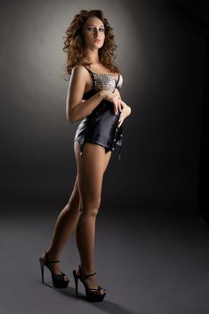 Foto de estudio de tentadora chica curtida en corsé de cuero