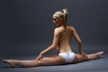 Rear view of young topless woman doing gymnastic split