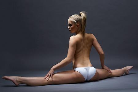fille nue sexy: Vue arrière du jeune seins nus femme faisant scission de gymnastique Banque d'images