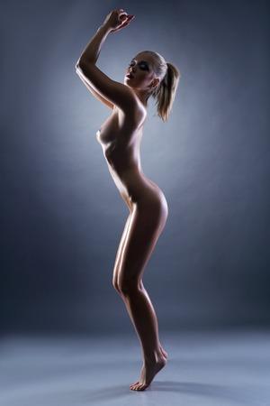 mujer desnuda: Agraciada mujer delgada posando desnuda en el estudio, sobre fondo gris