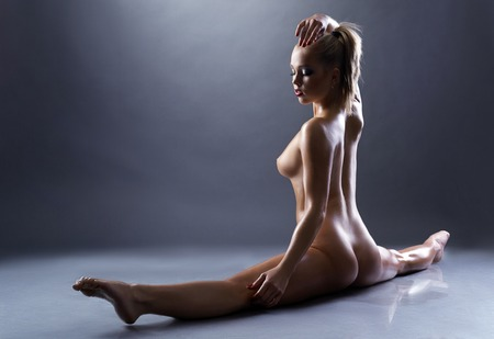 nude wet: Beautiful nude gymnast doing stretching exercise, on gray background Stock Photo