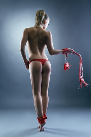 glamour nude: Studio shot of nude girl with BDSM attributes. Back view