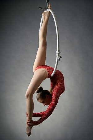 gymnastics equipment: Graceful acrobat performs gymnastic trick on hanging hoop Stock Photo