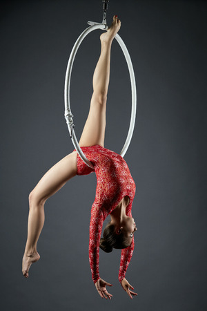 Studio photo of graceful dancer posing on aerial hoop Foto de archivo