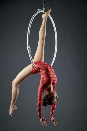 Studio foto van bevallige danser die zich voordeed op luchtfoto hoepel