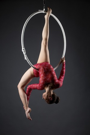 Sexy female acrobat exercising with hanging hoop in studio Banco de Imagens