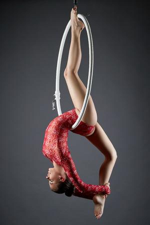 Studio photo of flexible dance performer on aerial hoop Foto de archivo