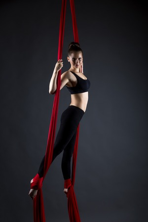 Image of smiling girl dancing with hanging ribbons in studio photo