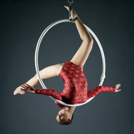 Studio photo of lovely gymnast performs acrobatic stunt on hoop