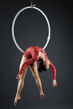 Image of beautiful aerialist doing gymnastic stunt on hoop Stock Photo