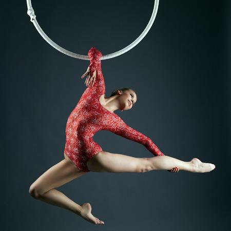 Studio shot van sierlijke vrouwelijke aerialist die zich voordeed op camera