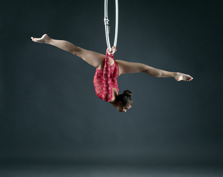 Flexible girl performs trick with hanging hoop, on gray background