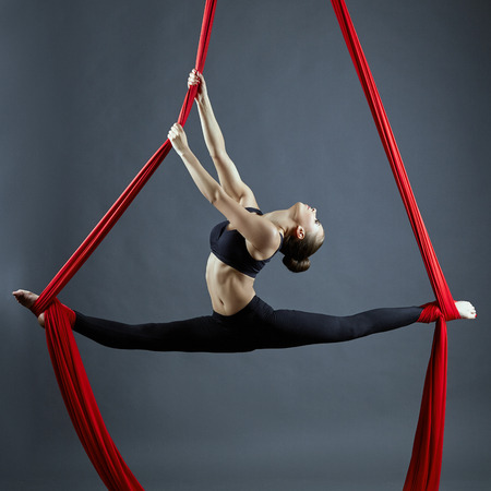 acrobat gymnast: Image of graceful gymnast performing aerial exercise Stock Photo