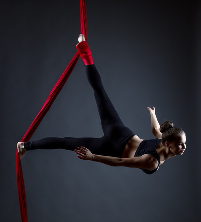 Studio shot of graceful female acrobat posing at camera