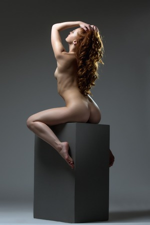 nude model: Red-haired woman with perfect body posing naked, on grey background