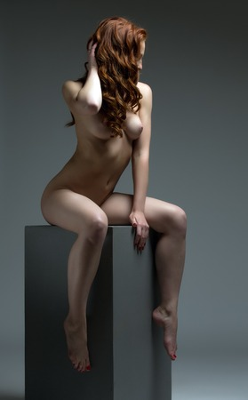 modelo desnuda: Foto del estudio. Modelo pelirroja posando desnuda, en el contexto gris