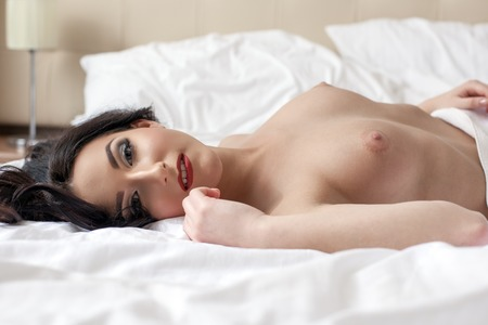 topless brunette: Gorgeous brunette posing naked while lying in hotel bed