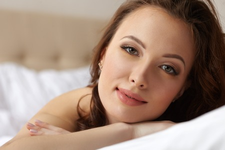 erotic woman: Portrait of pretty relaxed woman posing in hotel bedroom