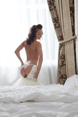 erotic dress: Rear view of sexy bride takes off her wedding dress in bedroom