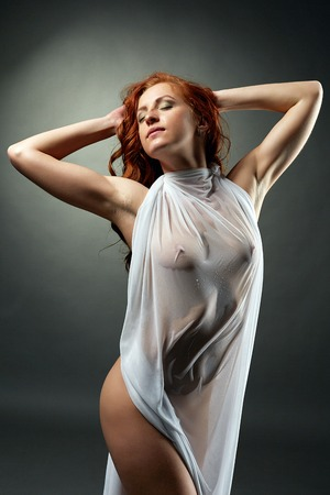 nude model: Red-haired naked woman posing in wet dress. Goosebumps on her body