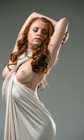 bare breast: Gorgeous red-haired beauty posing with naked breasts in tight dress