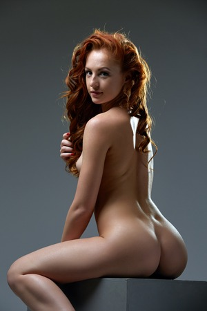 Image of curly red-haired beauty posing nude at camera