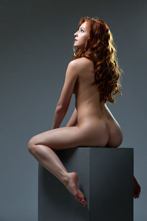 nude model: Curly red-haired beauty posing while sitting on big cube
