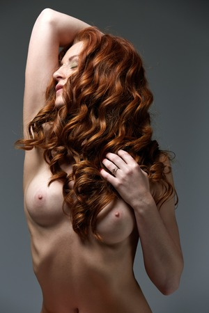 Curly red-haired beauty posing with naked perfect breasts