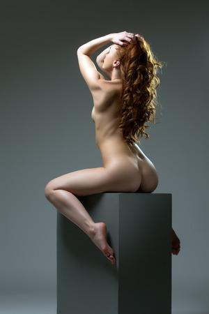 sexy nackte frau: Studioaufnahme der geschweiften rothaarige Frau sitzen auf großen Würfel Lizenzfreie Bilder