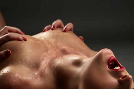 Оргазм понятие. Сексуальная стройная женщина сжимает грудь, макро Фото со стока