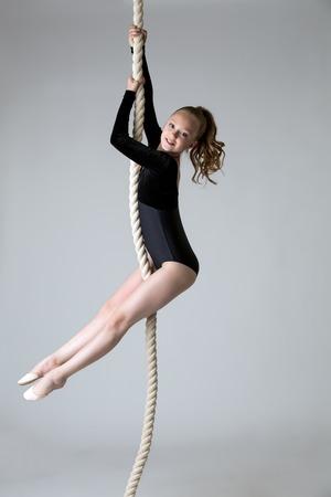 gymnastique: Charmant petit pouvoir gymnaste monte sur la corde en studio