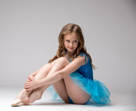Nice little ballerina smiling at camera, on grey background