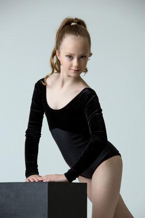 Studio photo of adorable little gymnast posing, on grey background Stock Photo