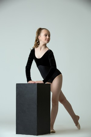 leotard: Graceful little gymnast posing with cube, on grey background Stock Photo