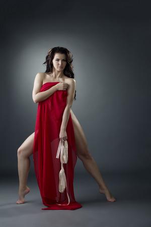 Charmante vrouwelijke danser flirty stellen bij camera terwijl het verbergen van rode doek Stockfoto