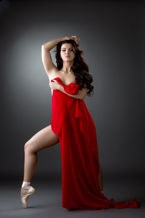 Pretty nude ballerina dancing with red cloth. Studio photo