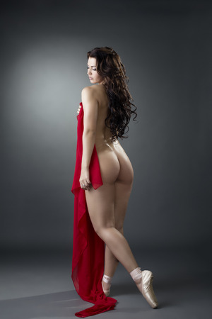 Rear view of sexy dancer posing naked with red cloth
